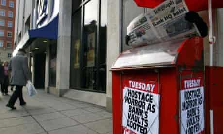 A newspaper seller outside the headquarters of the Northern Bank in Belfast the day after the robbery