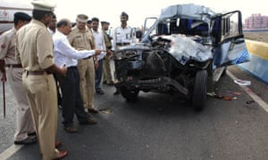 Policemen inspect a vehicle at the site of accident in Pune, India