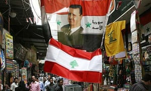 A flag carrying the face of the Syrian president, Bashar Assad, sits atop a  Lebanese flag in a market in Damascus