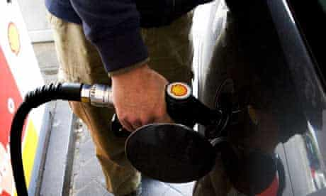 Person fills car at pump in petrol station