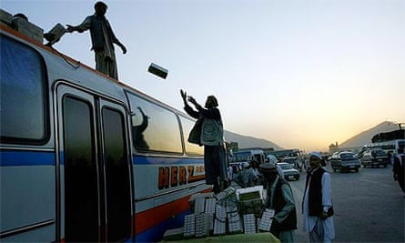 Afghan men load goods onto the top of a bus in Kabul