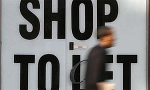 A pedestrian walks past a closed-down shop in the City of London