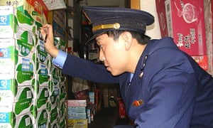 A Chinese trade enforcement officer checks boxes of milk at a shop in Tongzi, Guizhou province