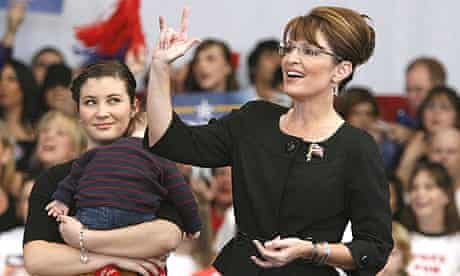 """Sarah Palin, with her daughter Willow, holding her brother Trig, campaigns at a rally in Henderson, Nevada. Palin is giving the American sign language hand sign for """"I Love You""""."""