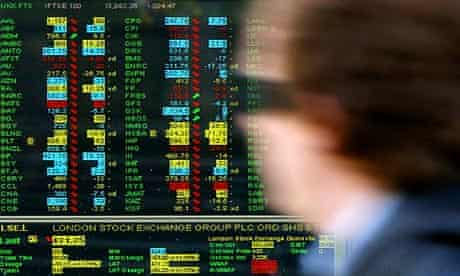 A worker walks past a screen displaying stock market movements at a window of the London Stock Exchange in the City of London, October 27, 2008