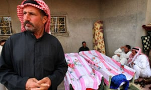 Syrians mourn next the bodies of their relatives who were killed in the US strike on the village of Sukkiraya