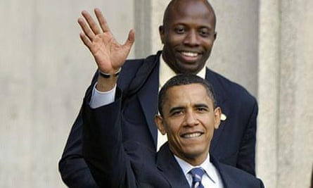 Democratic presidential candidate Barack Obama waves after leaving a fundraiser with his aid Reggie Love in Los Angeles