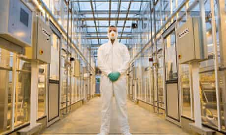 A British scientist wears a protective suit in a lab