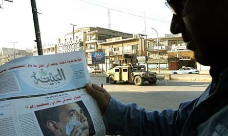 A man in Baghdad looks at a newspaper bearing an image of Barack Obama