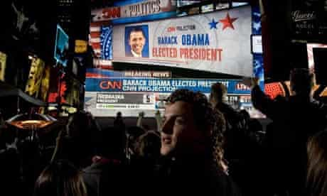 Barack Obama is show on a giant screen at an election night party in Times Square