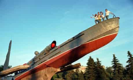 Tourists pose on a second world war assault ship that serves as a naval memorial in Kaliningrad