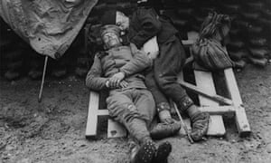 Two Serbian soldiers snatch some sleep in the trenches