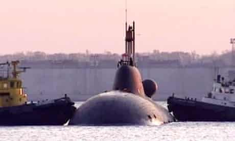 Tugs push the Nerpa into place at the Bolshoi Kamen naval base