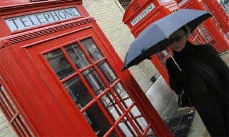 A woman walks past public telephone boxes in central London