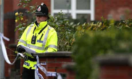 A police officer at the scene where a baby and a toddler were found dead on Kilmington Drive, Cheetham Hill, Manchester