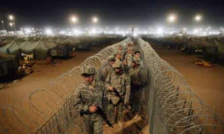 US troops walk along a corridor separating detainees at Camp Bucca in Iraq