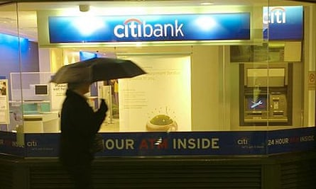A pedestrian walks past a branch of Citigroup bank in London, following the banking giant's announcement that it is to cut 50,000 jobs