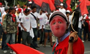 A masked supporter of the ruling Sandinista National Liberation Front party, FSLN, holds a homemade mortar during a protest in Managua. Photograph: Esteban Felix/AP