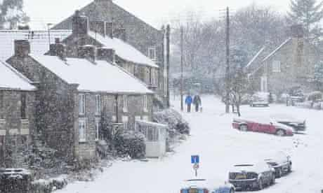 People walk a dog as snow falls in the village of Lockton, North Yorkshire