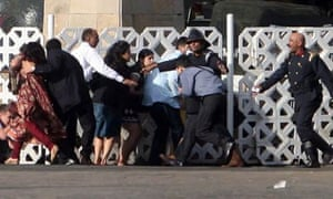 People take cover at the Taj Mahal hotel in Mumbai