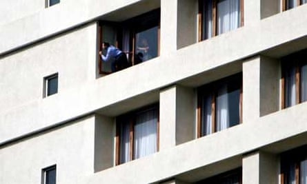A hostage peeks from a window at the Oberoi Trident hotel