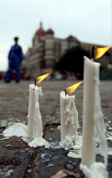 Candles burn for those who died in Mumbai as Indian soldiers stand guard outside the Taj Mahal hotel