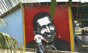 A man pushes his bicycle past a mural of Hugo Chávez in the president's home state of Barinas