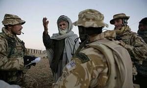 Royal Marines urge a village elder in Lashkar Gah to attend a community meeting with them