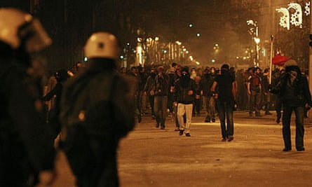 Protesters walk towards policemen during riots in Athens