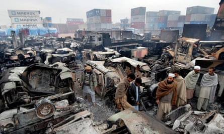 Pakistani employees inspect burned-out trucks outside the northwestern city of Peshawar