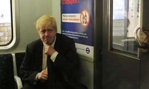 Boris Johnson adjusts his tie on an underground train