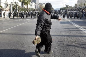 Gallery Greek Riots Continue: A protester throws rocks at riot police outside the Greek Parliament in