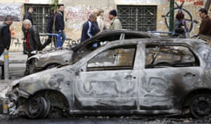 Gallery Greece riots: People walk past burned cars in Athens