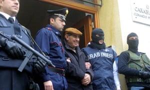 Italian police escort mafia suspect Giuseppe Scaduto (centre) from their headquarters in Palermo.