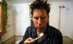 Man with hangover brushes teeth