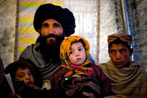 Gallery Life in Lashkar Gah: A man waits for a doctor to examine his child in a clinic in Lashkar Gah