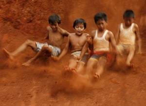 Gallery 24 hours in pictures: Children slide down a slope in Jakarta