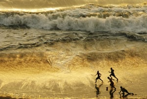 Gallery 24 hours in pictures: Children play football during sunset at a beach in Lima