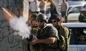 Israeli border police officer fires a tear gas canister