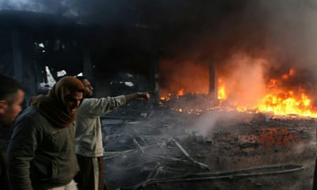 Palestinian men look on as flames rise from debris at the site of an Israeli air strike in Rafah, Gaza