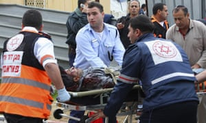 Israeli medics evacuate an injured man from the scene of a rocket attack in the city of Ashkelon