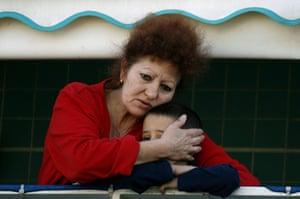 Gallery Ashkelon: Israeli woman hugs boy at scene of rocket attack