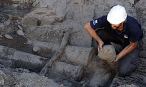 An archaeologist holds a cannonball of a Spanish galleon at a Buenos Aires building site.