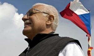 A Czech flag waves behind Czech President Vaclav Klaus as he stands on Snezka mountain