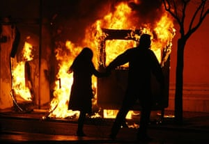 Gallery Riots in Athens: A couple runs to escape a fire at a booth during riots in Athens
