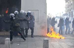 Gallery Riots in Athens: A petrol bomb burns next to riot police during trouble in Thessaloniki