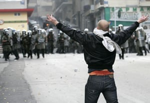 Gallery Riots in Athens: A protester taunts riot police in Athens