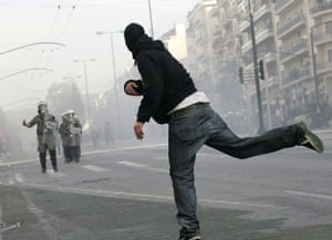 Gallery Riots in Athens: A protester throws stones at riot policemen during riots in Athens