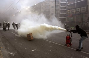 Gallery Riots in Athens: A demonstrator sets a fire extinguisher on the police