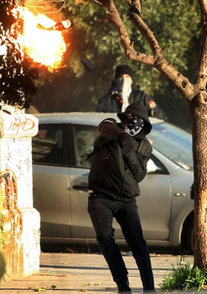 Gallery Riots in Athens: A protestor throws a petrol bomb at riot police in Thessaloniki